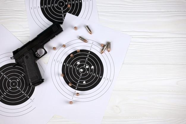 총과 많은 총알이 사격장 다각형의 흰색 테이블에 표적을 쏘고 있습니다.