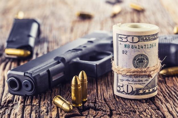 Пистолет и деньги. пули 9-миллиметрового пистолета разбросаны и катятся долларовые банкноты по деревенскому дубовому столу.