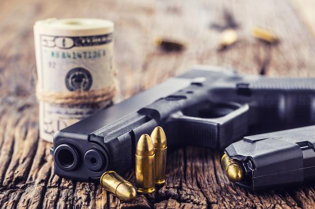 銃とお金。素朴なオーク材のテーブルに9mmのピストル銃の弾丸が散らばり、ドル紙幣を転がします。