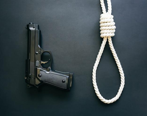 총과 올가미가 검은 배경에 누워 있습니다. 자살 개념입니다. 교수형 또는 살인.