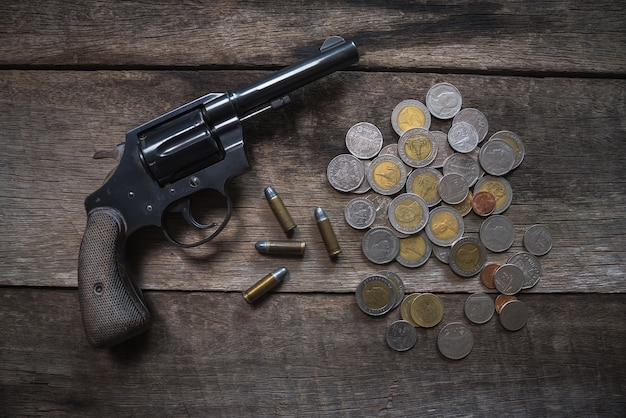 Gun and coins on wooden table. top view