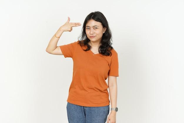 흰색 배경에 고립 된 오렌지 티셔츠를 입고 아름 다운 아시아 여자의 머리에 총 손가락