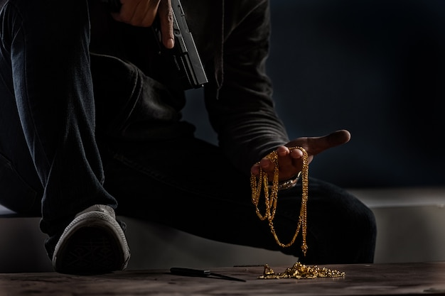 Gun and gold in hands
