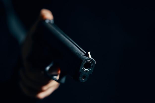 攻撃または防御のための暗い背景の銃のクローズアップピストルに男の手で銃