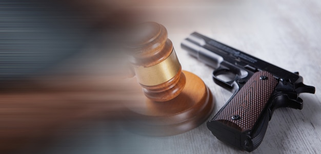 A gun and a judge's hammer on the table