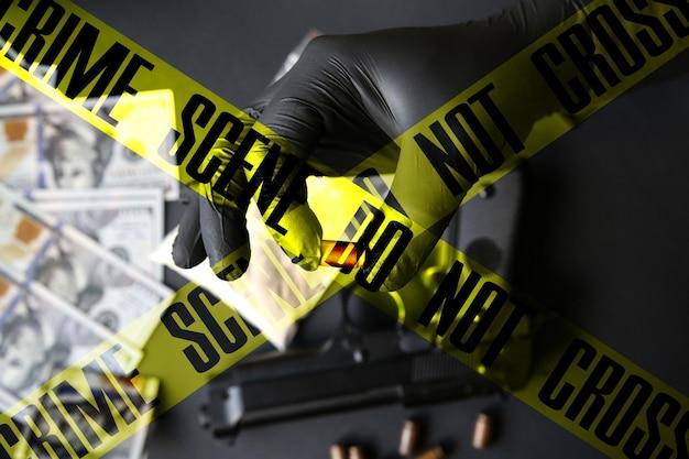 테이블에 누워 총입니다. 총알을 들고 검은 장갑에 남자입니다. 불법 마약 판매. 범죄 현장은 테이프를 교차하지 않습니다. 불화.