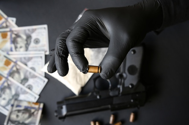 テーブルの上に横たわっている銃。弾丸を保持している黒い手袋の男。違法薬物の販売。刑事問題。ドル。