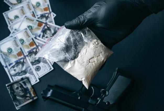 テーブルの上に横たわっている銃。薬を保持している黒い手袋をはめた男。違法な販売。刑事問題。
