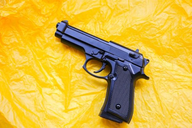 Пистолет, лежащий на желтом фоне. легализация оружия. понятие преступления.