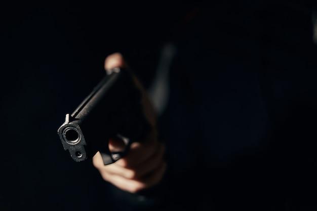 Gun in mans hand on dark background firearms closeup pistol for attack or defense criminal concept