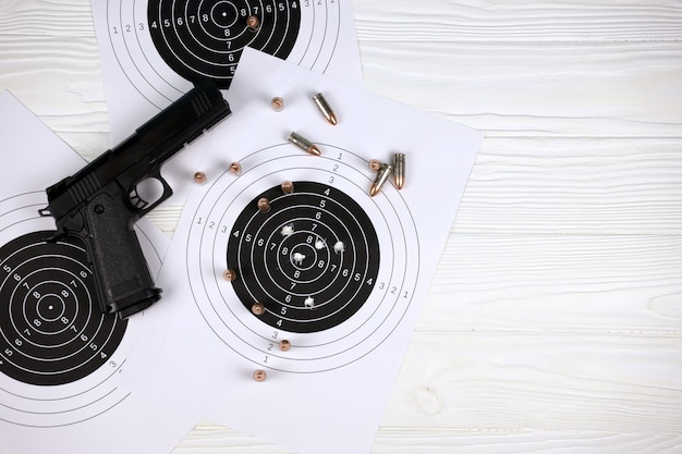 Gun and many bullets shooting targets on white table in shooting range polygon.
