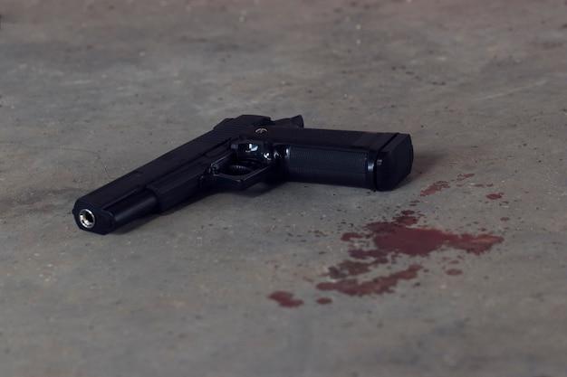 血の染みが付いたセメントの床に置かれた銃