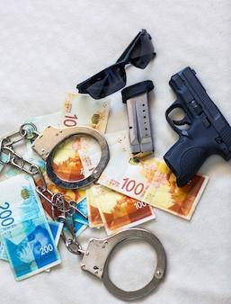 イスラエルの新シェケル紙幣のお金の背景に銃警察手錠サングラス