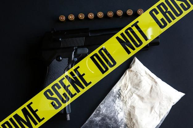 テーブルの上に弾丸が横たわっている銃。犯罪現場はテープを交差させません。薬と黒の背景に。違法な販売。