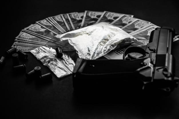 テーブルの上に弾丸が横たわっている銃。刑事問題。黒の背景に薬とお金。違法な販売。黒と白の写真。