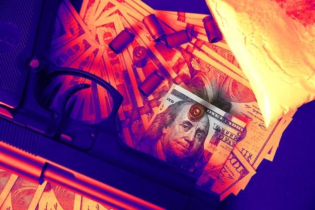 テーブルの上に弾丸が横たわっている銃。刑事問題。黒の背景に薬とお金。違法な販売。ドル。