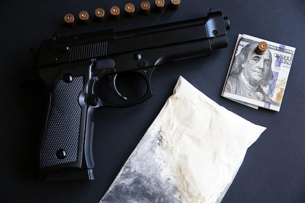 テーブルの上に弾丸が横たわっている銃。刑事問題。黒の背景に薬とお金。違法な販売。