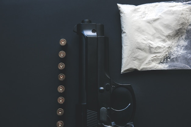 テーブルの上に弾丸が横たわっている銃。刑事問題。薬と黒の背景に。違法な販売。