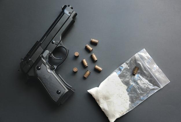 테이블에 누워 총알과 총입니다. 범죄 문제. 패킷에 있는 마약. 불법 판매.
