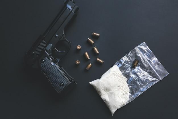 テーブルの上に弾丸が横たわっている銃。刑事問題。パケット内の薬。違法な販売。