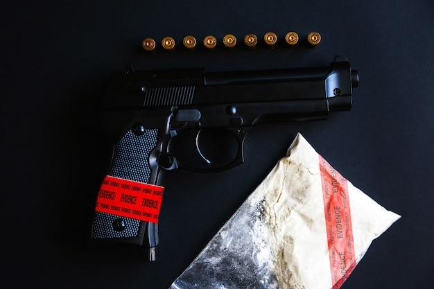 テーブルの上に弾丸が横たわっている銃。刑事問題。証拠のサイン。違法な販売。