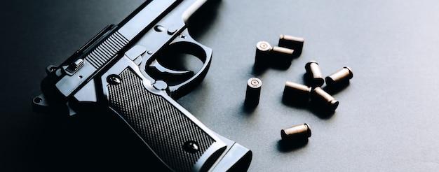 テーブルの上に弾丸が横たわっている銃。武器の合法化。刑事問題。