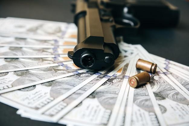 Пистолет с пулями, лежащими на столе. деньги на черном фоне. криминальные проблемы. долларов.