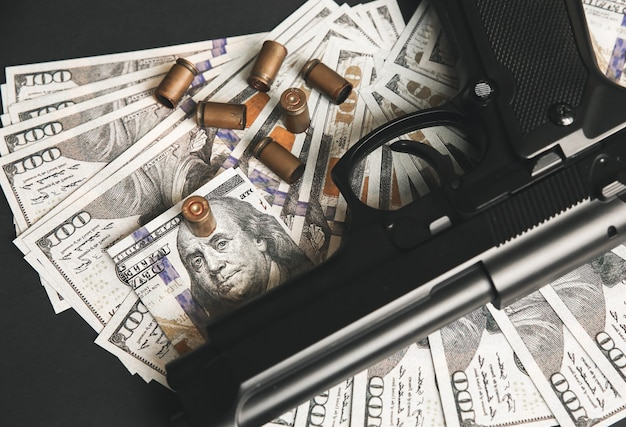 Gun with bullets lying on the table. money on black background. criminal problems. dollars.