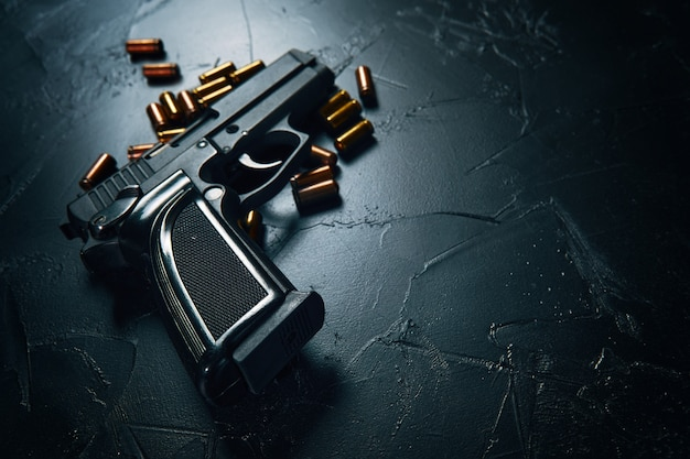 コンクリートのテーブルに弾丸が付いた銃銃のクローズアップ犯罪の武器防御または攻撃黒いピストルと真ちゅう製のカートリッジはテキスト用のスペースをコピーします