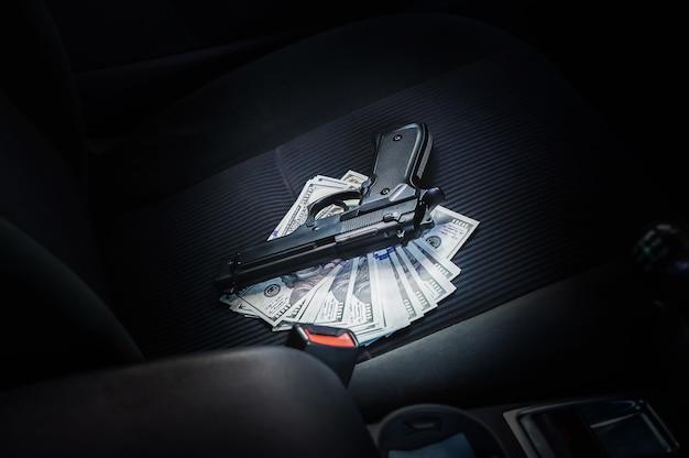 Пистолет с деньгами, лежащий в машине. угон автомобиля. грабежи и преступление.