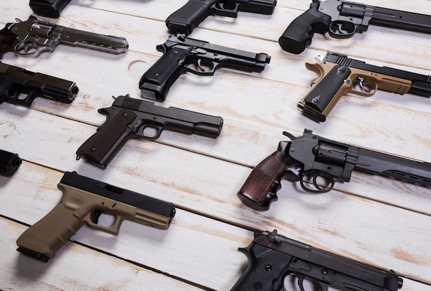 Огнестрельное оружие. gun. крупный план оружие лежит на деревянной белой предпосылке.