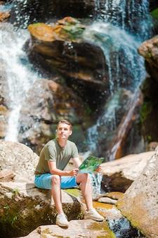 Человек, наслаждаясь видом на водопад в gungle