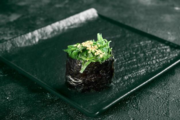 Гункан маки суши с водорослями хияши на черной доске с имбирем и васаби. японская кухня. доставка еды. черный фон