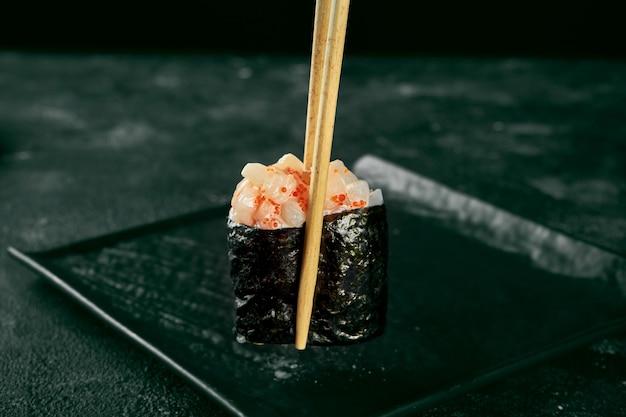 Гункан маки суши с лососем и острым соусом на черной доске с имбирем и васаби. японская кухня. доставка еды. черный фон. палочки держат суши