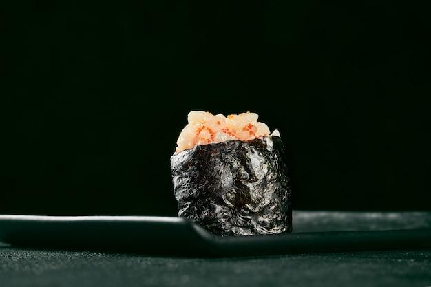 Гункан маки суши с лососем и острым соусом на черной доске с имбирем и васаби. японская кухня. доставка еды. черный фон
