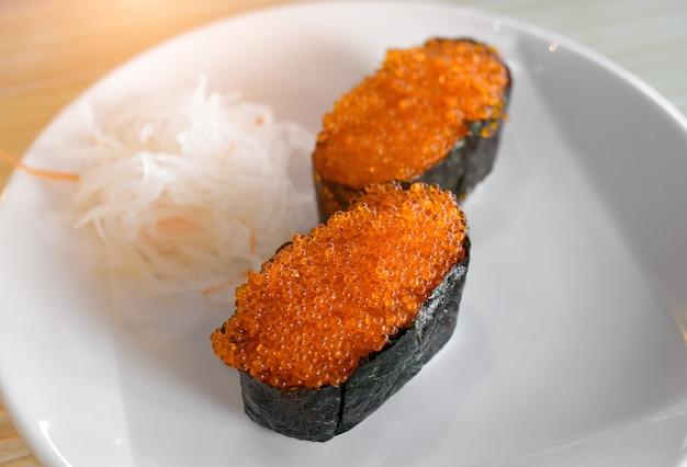 실내 조명이 낮은 흰색 접시에 있는 토비코 날치알의 군칸 스시.