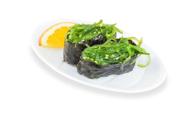 Гункан суши с вакаме with hiashi и огурцом с кунжутом на белой тарелке с золотой каймой. паназиатское меню ресторана