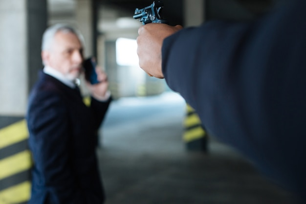 At gunpoint. selective focus of a handgun directed at the businessman while being in hands of a dangerous hardened criminal