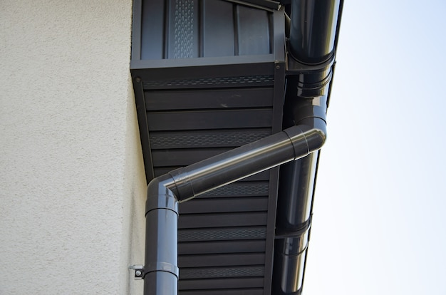 Gutter with downpipe on the roof of a house.