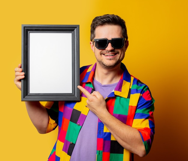 Guy in 90s shirt and sunglasses with photo frame