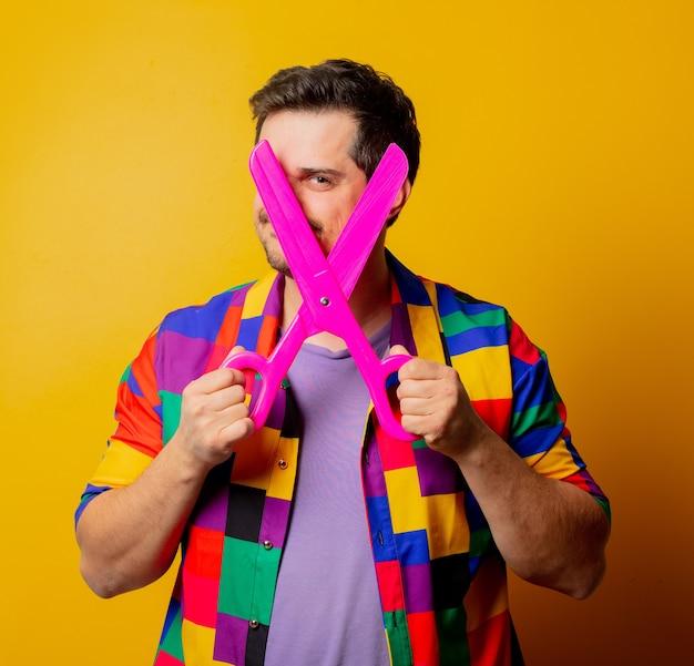 Guy in 90s shirt with big scissors
