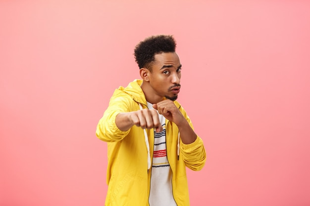 Guy acting cool bragging in front of girlfriend with mascules showing boxer moves standing in boxing pose with raised fist in punch gesture turning right as if fighting over pink background