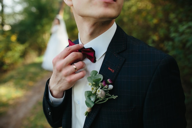 Guy adjusting bowtie standing in forest