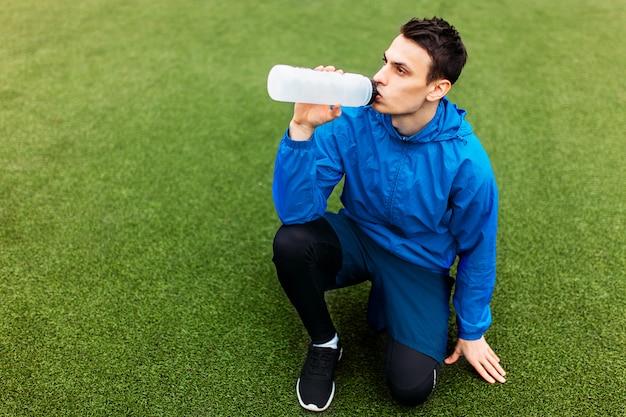 運動後の男、サッカー場の飲料水。スポーツウェアの美しい男の肖像画。
