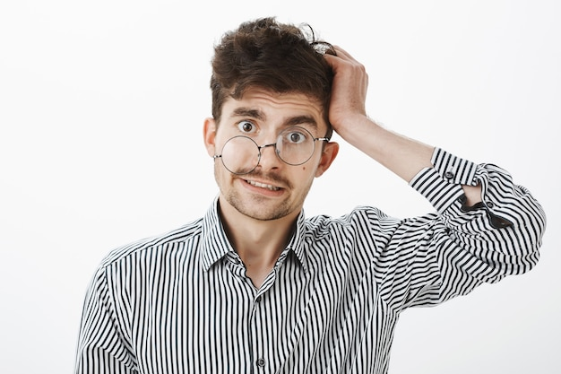 Guy after hangover lost memory. confused questioned messy male in striped shirt, scratching hair and looking unaware and clueless with glance from under glasses, standing over gray wall
