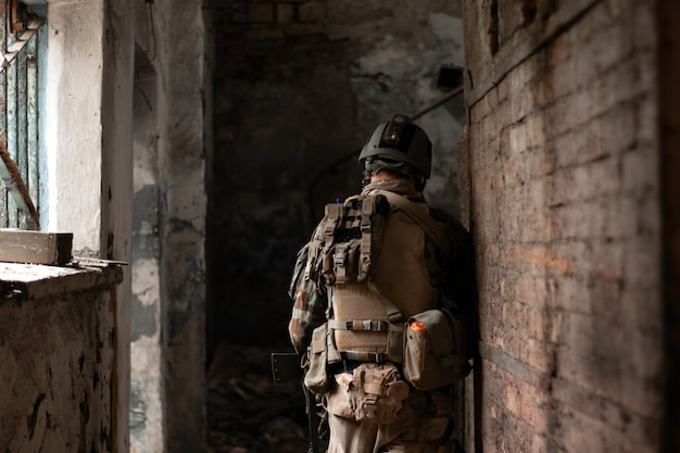 A guy in an american military uniform in an old abandoned aisle moves with a gun airsoft sports gam