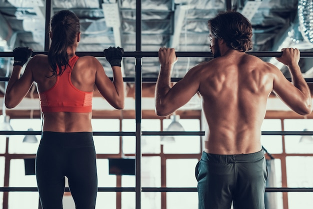 남자와 여자는 체육관에서 풀업을하고 있습니다.