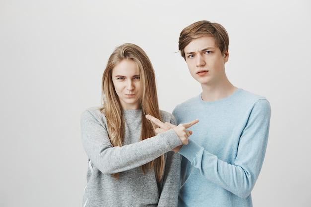 Парень и девушка обвиняют друг друга. братья и сестры, указывая пальцами.