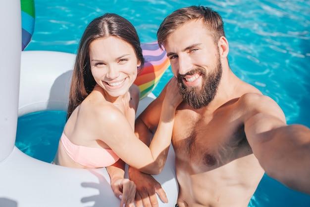 男と女はプールにいます。彼女はエアマットレスにいます。若い男はカメラを保持しています。彼らはそれを見て、笑顔になります。 grlは男に傾いています。