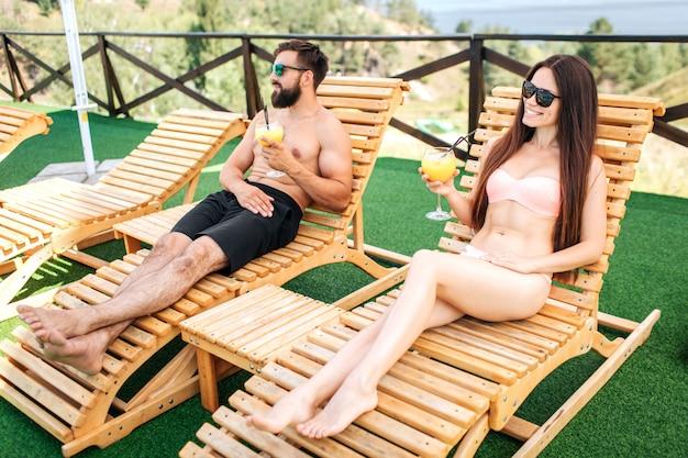 Парень и девушка отдыхают на лежаках и смотрят налево. они держат в руках бокалы для коктейлей. девушка позирует они носят солнцезащитные очки.